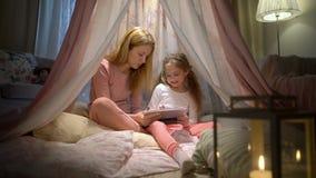Mãe nova e sua filha que têm o divertimento usando a tabuleta que joga apps vídeos de arquivo