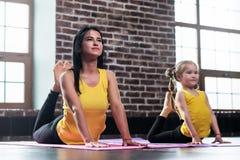 A mãe nova e sua filha que vestem o mesmo sportswear que faz a cobra de rei levantam durante o treinamento da ioga do grupo imagens de stock royalty free