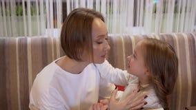 A mãe nova e uma filha pequena de encantamento sussurram secretamente algo na orelha