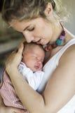 Mãe nova em casa que guarda sua filha recém-nascida do bebê imagem de stock