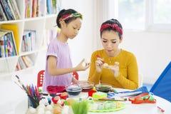 A mãe nova ensina sua filha pintar ovos imagem de stock