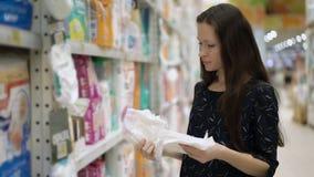 A mãe nova escolhe o tecido para seu interior da criança do mercado, suportes da menina perto da prateleira do supermercado e sel filme