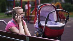 A mãe nova fala ao telefone no campo de jogos Transporte de bebê vermelho Miúdos Banco video estoque
