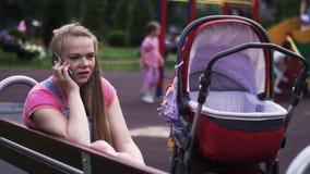 A mãe nova fala ao telefone no campo de jogos Transporte de bebê vermelho Miúdos Sorriso video estoque