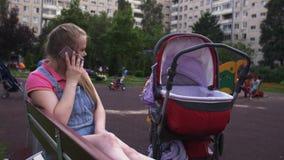 A mãe nova fala ao telefone no campo de jogos Transporte de bebê vermelho Miúdos verão filme