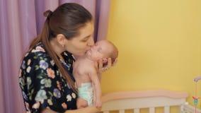 A mãe nova feliz agita seu bebê em seus braços ao beijá-lo video estoque