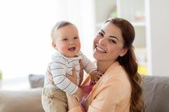 Mãe nova feliz com bebê pequeno em casa Fotos de Stock Royalty Free