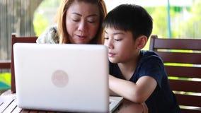 Mãe nova, feliz com a criança que usa o portátil no terraço vídeos de arquivo