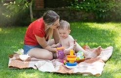 Mãe nova feliz com seus 10 meses do bebê idoso no piquenique da família no parque Fotografia de Stock