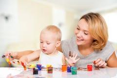 Mãe nova feliz com uma pintura do bebê pelas mãos. Imagem de Stock