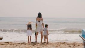 Mãe nova feliz da vista traseira com o rapaz pequeno e a menina que olham as ondas em férias no movimento lento da praia tropical vídeos de arquivo