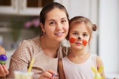 Mãe nova feliz e sua filha pequena com a cara pintada na cozinha clara acolhedor imagem de stock