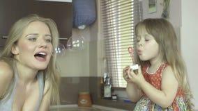 Mãe nova feliz e suas bolhas de sabão de sopro da filha na cozinha video estoque
