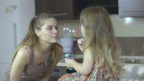 Mãe nova feliz e suas bolhas de sabão de sopro da filha na cozinha filme