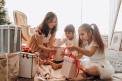 Mãe nova feliz e suas duas filhas de encantamento no dresse agradável fotografia de stock