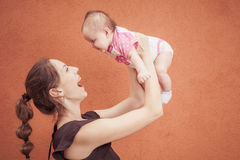 A mãe nova feliz joga acima o bebê na parede da laranja do fundo Fotografia de Stock Royalty Free