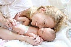 Mãe nova feliz que aconchega-se a filha recém-nascida do bebê na cama Imagens de Stock