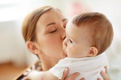 Mãe nova feliz que beija o bebê pequeno em casa Imagem de Stock Royalty Free