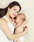 Mãe nova feliz que dorme com o bebê na cama em casa, t Imagens de Stock