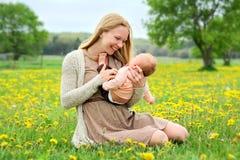 Mãe nova feliz que joga com bebê recém-nascido fora Imagem de Stock