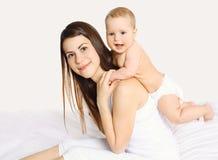 Mãe nova feliz que joga com o bebê na cama Imagem de Stock Royalty Free