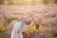 Mãe nova feliz que joga sua criança de riso Fotografia de Stock Royalty Free
