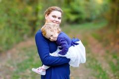 Mãe nova feliz que tem a filha bonito da criança do divertimento, retrato da família junto Mulher com o bebê bonito na natureza imagens de stock