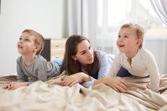 Mãe nova feliz vestida em claro - o pijama azul coloca com seus dois poucos filhos na cama com a cobertura bege no imagens de stock royalty free