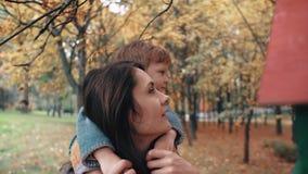 A mãe nova guarda em ombros rapaz pequeno bonito, rapaz pequeno abraça seus alimentadores próximos do pássaro no parque surpreend video estoque