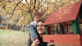 A mãe nova guarda em ombros rapaz pequeno bonito, rapaz pequeno que os abraços beijam seus alimentadores próximos do pássaro no p filme