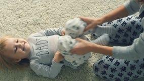 A mãe nova joga com a filha no assoalho video estoque