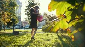 A mãe nova joga com o filho pequeno no parque do verão no por do sol - lento-movimento video estoque