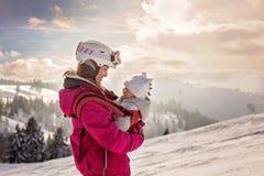 Mãe nova, levando seu bebê no estilingue, escalando no pico w imagem de stock