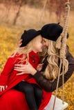 A mãe nova muito bonita que abraçam sua filha pequena e estão rindo alegremente contra o contexto do jardim do outono foto de stock