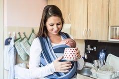 Mãe nova na cozinha com seu filho no estilingue fotografia de stock royalty free