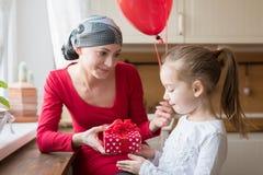 Mãe nova, paciente que sofre de câncer, e sua filha bonito, comemorando o aniversário com balões e presentes Imagem de Stock