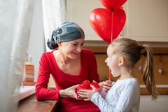Mãe nova, paciente que sofre de câncer, e sua filha bonito, comemorando o aniversário com balões e presentes Fotos de Stock