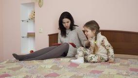 A mãe nova pergunta a sua filha pequena don o ` t perturba-a durante o trabalho vídeos de arquivo