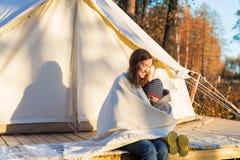 Mãe nova que abraça sua criança com uma cobertura ao sentar-se perto da barraca de sino da lona fotografia de stock