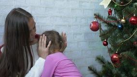 Mãe nova que abraça sua filha pequena de grito ao lado da árvore de Natal video estoque