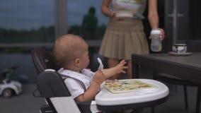 Mãe nova que alimenta seu filho do bebê que senta-se em um assento da criança - cena morna do verão da cor dos valores familiares filme