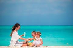 Mãe nova que aplica a proteção solar em suas crianças imagem de stock