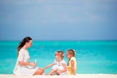 Mãe nova que aplica a proteção solar em suas crianças na praia imagem de stock