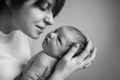 Mãe nova que beija seu bebê recém-nascido pequeno Fotografia de Stock