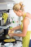 Mãe nova que cozinha em casa Foto de Stock Royalty Free