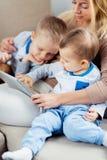 Mãe nova que embosoming dois filhos que jogam a tabuleta digital imagens de stock royalty free
