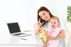 Mãe nova que guarda o bebê ao falar no telefone imagens de stock