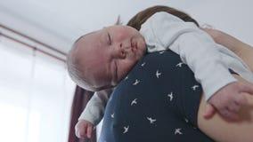 Mãe nova que guarda seu bebê em seu ombro filme