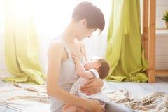 Mãe nova que guarda sua criança recém-nascida Bebê dos cuidados da mamã em um quarto branco Interior do berçário Família em casa foto de stock