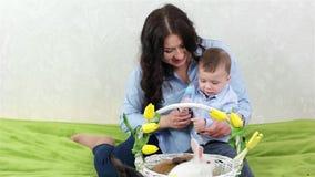 Mãe nova que joga com filho, mamã que senta-se com criança, criança que tem o divertimento com ovos coloridos video estoque